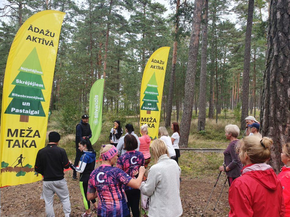 Meža takas atklāšanas pasākums. Daudz cilvēki - nūjotāji mežā pirms takas atklāšanas.