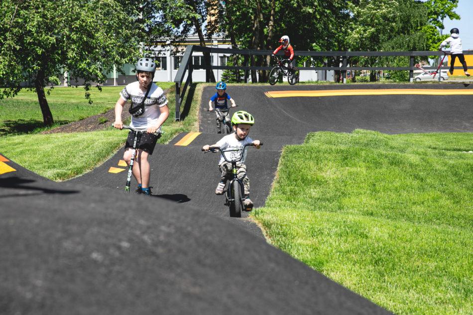 Bērni brauc ar velosipēdiem pa velo pumpu trasi
